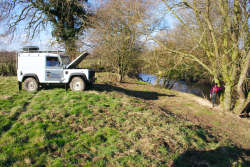 Landrover winching timber on to top of the bank
